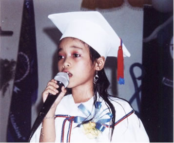 Girl in white graduation cap and robe singing at microphone.